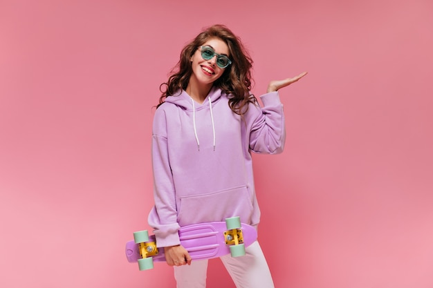 Charming girl in purple hoodie and white pants smiles and holds colorful longboard