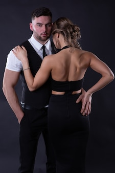 Charming girl put her hand on the shoulder of a man in love with her, who gently hugs her waist