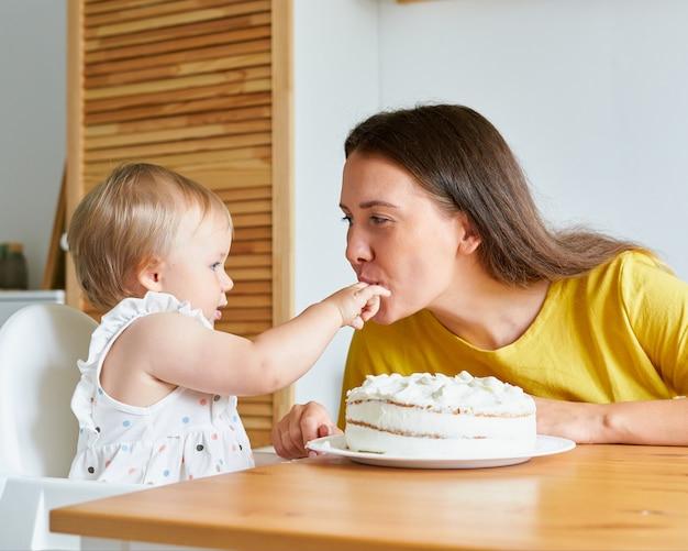 Очаровательная девушка кладет в рот мамаше нежнее с кремом от торта веселая мама с малышом