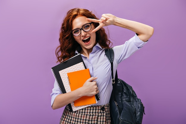 Charming girl in shirt and eyeglasses holds notebooks, shows peace sign