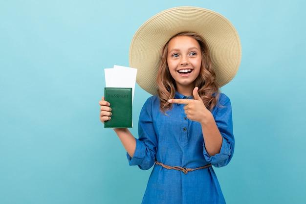 Очаровательная девушка показывает паспорт с билетами и радуется