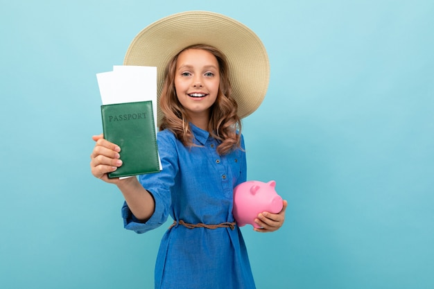 Charming girl shows a passport with tickets, holds a pink pig moneybox and rejoices