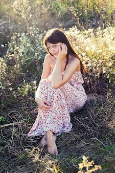 花のマキシドレスで夏の終わりの牧草地に裸足で座っている魅力的な女の子