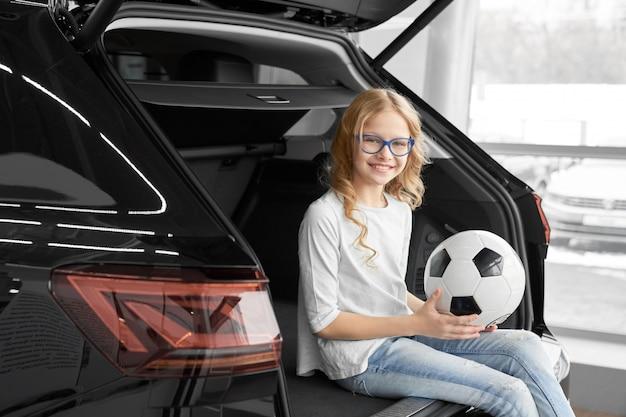 Charming girl sitting in car trunk of dealership showroom.
