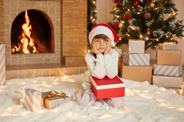 Charming girl sitting on floor with present box, keeping palms on cheeks, looks bored, waiting for opening gifts, posing with xmas tree and fireplace, wears santa hat.