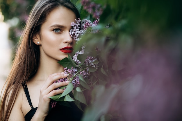 The charming girl stands near bushes with flowers