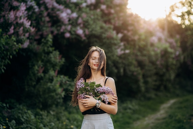 The charming girl stands in the park and keeps a bouquet