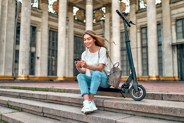 A charming girl student sits on the steps on a scooter near the campus and uses her smartphone.