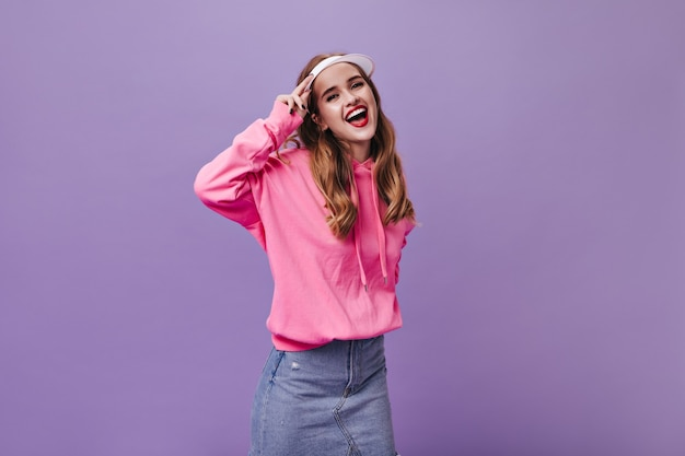 Charming girl in stylish street outfit laughing on purple wall
