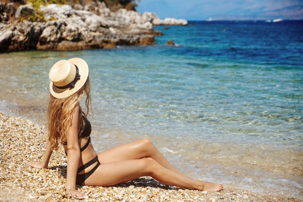 Charming girl sunbathing on beach in bikini and straw hat