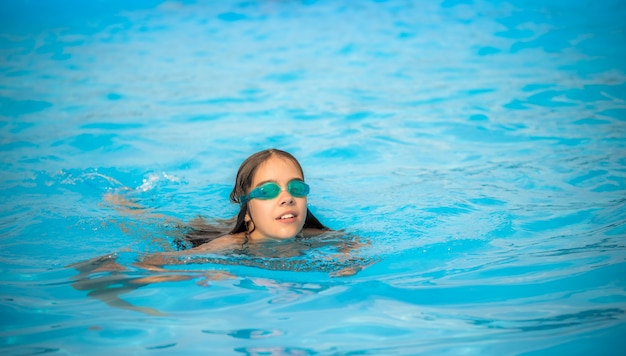 Charming girl teenager wearing waterproof glasses for the pool swims
