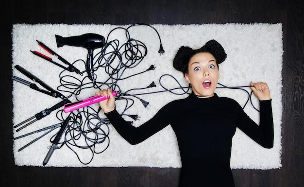 頭にドレッドヘアのある美容師の魅力的な女の子は、ヘアアイロンの紐で首を絞め、カメラを見ています。散髪を作成するためにレイアウトされたアイテムを背景に