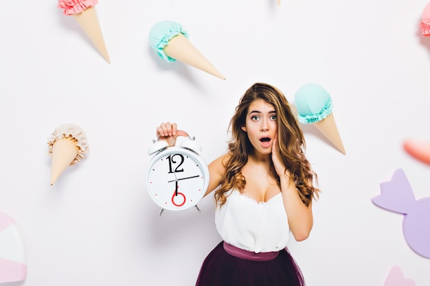 Charming girl wearing luxury dress posing with surprised face expression on cute wall with sweet decor. portrait of worried young woman with shiny hair holding big clock.