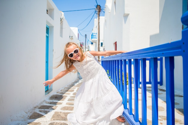 Charming girl in white dress outdoors in old streets an mykonos. kid at street of typical greek traditional village with white walls and colorful doors on mykonos island, in greece