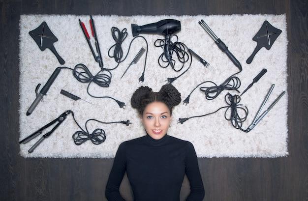 Очаровательная девушка с серьезным взглядом лежит на белом ковре. на фоне инструментов для создания стрижки