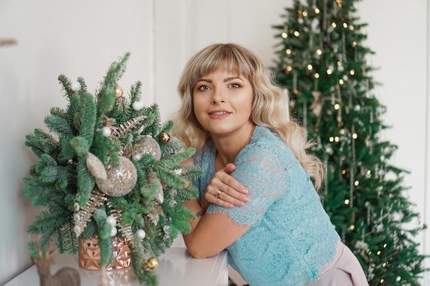 가족과 함께 금색과 흰색 인테리어 크리스마스 휴일 메리 축하의 얼굴에 아름다운 메이크업으로 매력적인 소녀