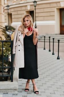 Очаровательная девушка со светлыми волосами идет по улице в черном плиссированном платье, радуется хорошей погоде в выходные