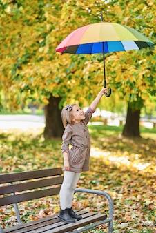 가을 공원에서 화려한 우산을 쓴 매력적인 소녀