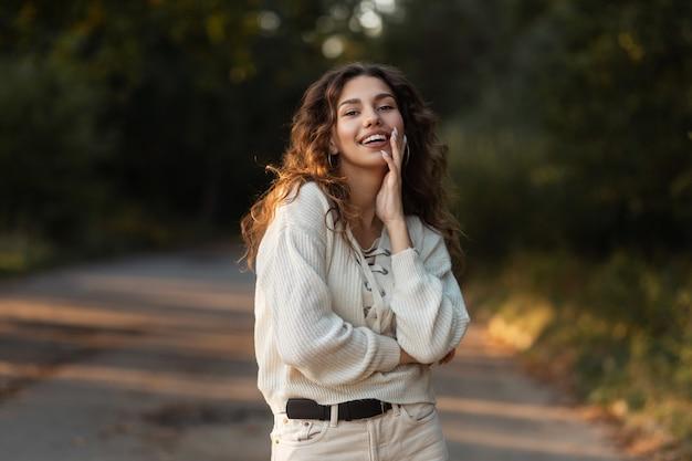 곱슬머리에 세련된 가을 스웨터를 입은 하얀 미소를 가진 매력적인 소녀