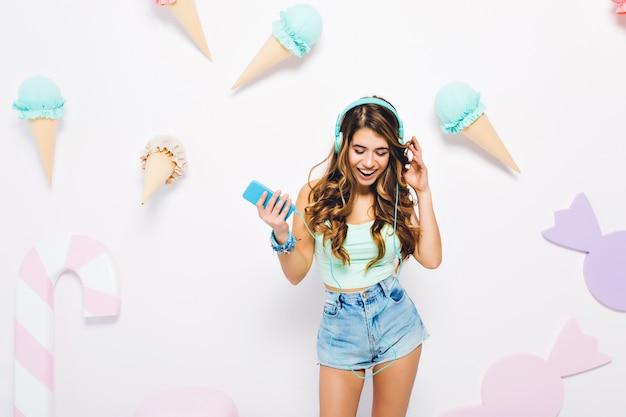 明るい茶色の巻き毛の笑顔で音楽を聴き、見下ろしている魅力的な女の子。デニムショートパンツとアイスクリームで飾られた壁でポーズのイヤホンで格好の良い若い女性の肖像画。