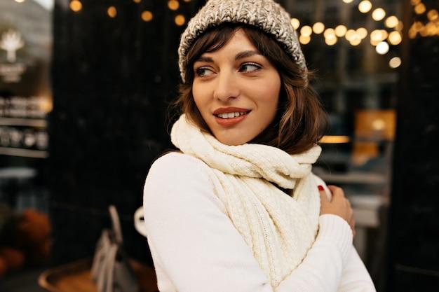 Affascinante ragazza con lunghi capelli scuri in cappello lavorato a maglia