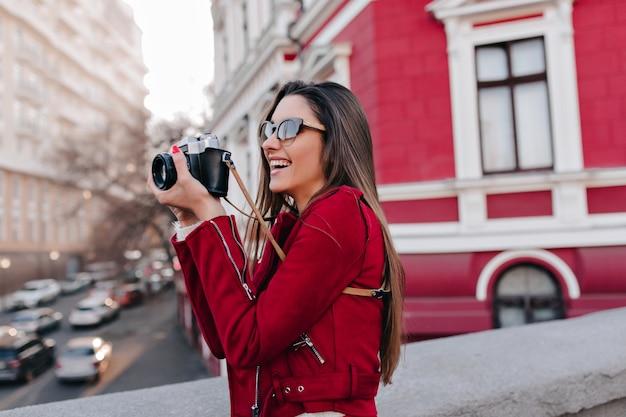 Affascinante ragazza con lunghi capelli lisci, scattare una foto della città