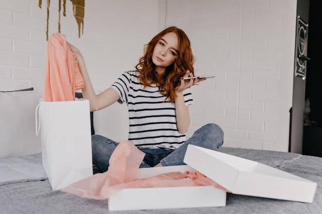 ベッドに座っている電話を持つ魅力的な女の子。週末にリラックスできるジーンズのジョクンド女性モデル。