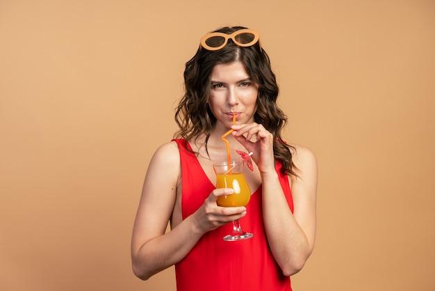 オレンジ色の背景にカクテルを飲む彼女の頭にサングラスをかけた魅力的な女の子