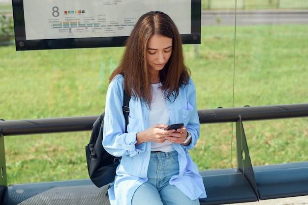 Charming girl with trendy look use smart phone while waiting on bus stop. woman holds mobile phone while sitting on a public station and waiting for taxi.