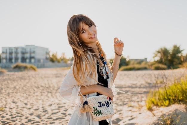 물결 모양의 갈색 머리 머리카락을 가진 매력적인 소녀, 흰색 boho 덮개를 입고 화창한 여름 해변을 걷고 있습니다. 여행 및 휴가 개념.