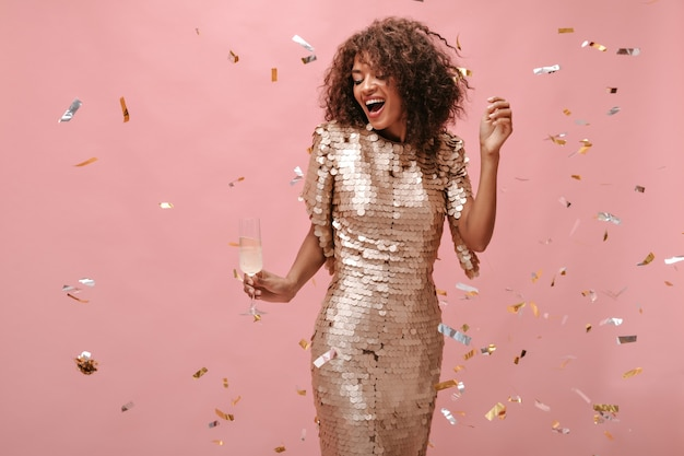 シャンパンとガラスを保持し、ピンクの壁に紙吹雪でポーズをとる光沢のあるベージュのドレスの波状の短い髪の魅力的な女の子。