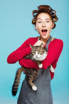 Charming girl with wide smile with cat in hands poses