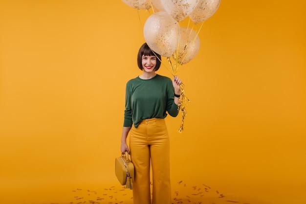 파티 후 미소로 포즈를 취하는 노란색 핸드백으로 매력적인 소녀. 풍선과 함께 아름 다운 갈색 머리 아가씨의 실내 사진입니다.