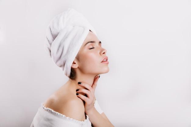 化粧をしていない魅力的な女の子が首を優しくマッサージします。白い壁にポーズをとって完璧な肌を持つ女性。