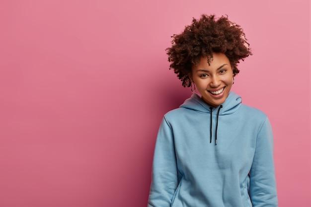 魅力的な嬉しいアフロアメリカ人女性は前向きに笑う