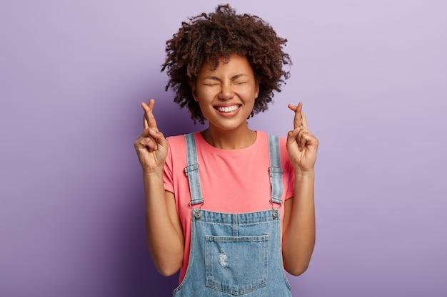 魅力的な嬉しい女性は夢が叶うのを待って、幸運のために指を交差させ、歯を見せる笑顔を持ち、目を閉じ、成功を目指します
