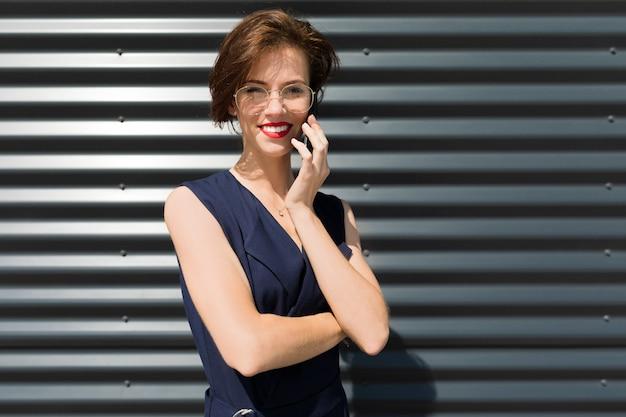 赤い唇と電話で話している魅力的な魅力的なビジネスの女性、外の建物の壁の