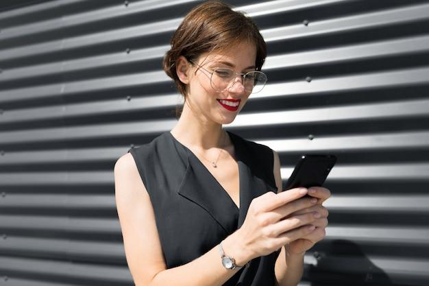 外の建物の壁を背景に彼女の手に電話で赤い唇を持つ魅力的な魅力的なビジネス女性