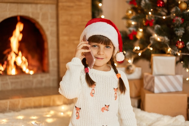 Charming good looking female child talking on phone to somebody, congratulating, having two pigtails, wearing santa hat, while posing in living room with christmas decoration.