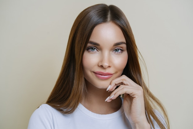 Charming good looking millennial woman keeps hand near face, has healthy glowing skin, dark hair, blue eyes, dressed in casual wear. human face expressions concept