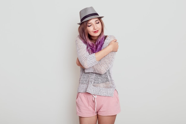 Charming gorgeous european woman keeps eyes closed, smiles with pleasure, feels comfort, hugs herself, wearing hat, shirt and short, isolated over grey background.
