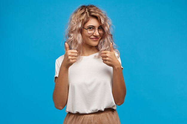 Charming gorgeous young female hipster with voluminous pinkish hair smiling happily at camera, showing thumbs up gesture