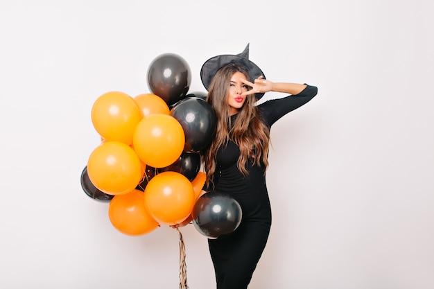 Affascinante donna graziosa in cappello della strega che tiene palloncini di elio