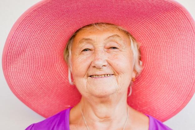 青い目と優しい笑顔のピンクの帽子の魅力的な祖母