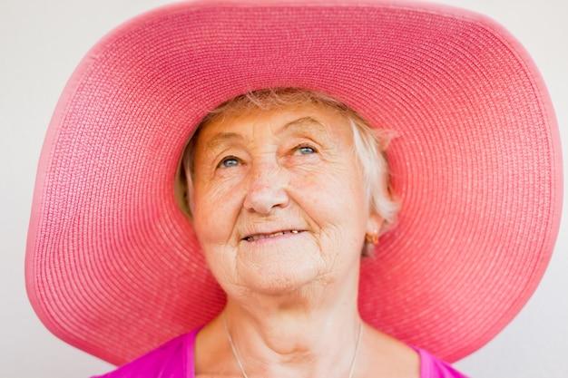 Очаровательная бабушка в розовой шапке с голубыми глазами и нежной улыбкой