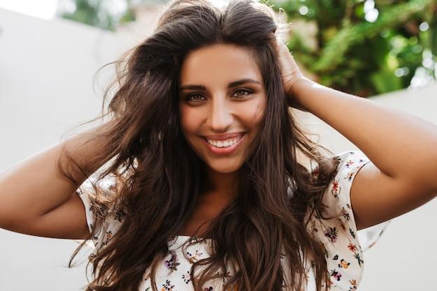 Очаровательная зеленоглазая женщина трогает свои длинные темные волосы и улыбается, глядя вперед на белой стене с растениями