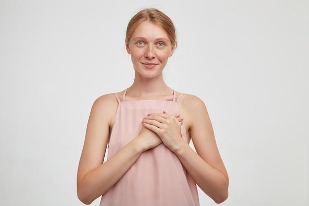Affascinante femmina giovane rossa dagli occhi verdi con acconciatura casual che tiene le mani alzate sul suo cuore e che guarda l'obbiettivo con un sorriso piacevole, isolato sopra priorità bassa bianca