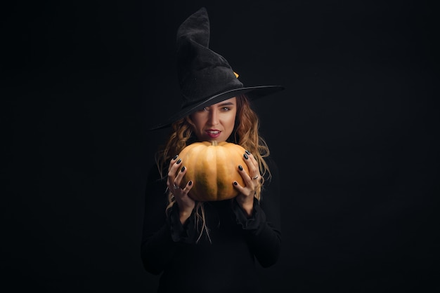 Charming halloween witch over black wall