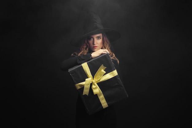 검은 벽에 매력적인 할로윈 마녀