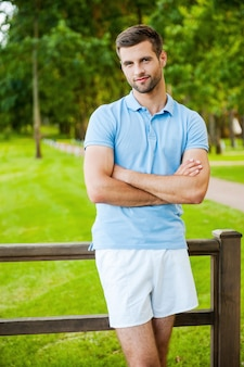 Charming handsome. handsome young man keeping arms crossed and smiling while standing outdoors and leaning at the fence